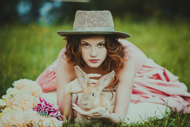 beautiful girl with a rabbit outdoors in summer day