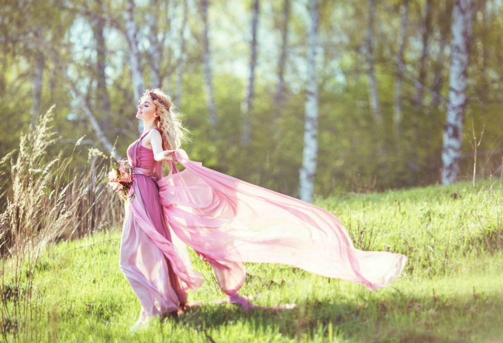 Beautiful blonde girl in a pink dress on a long evolving nature background